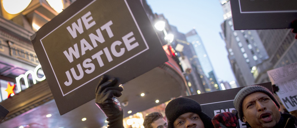 A protester holds up a sign while demonstrating outside of Macy's in Herald Square during the Black Friday shopping day in New York November 28, 2014. More than 200 people angered by a grand jury's decision not to indict a white police officer for killing unarmed black teenager Michael Brown in Ferguson, Missouri, sought to disrupt Black Friday shopping in New York with a protest in front of Macy's flagship store. Many protesters said they were encouraging a boycott of Black Friday to highlight the purchasing power of black Americans and to draw links between economic inequality and racial inequality. REUTERS/Brendan McDermid (UNITED STATES - Tags: CRIME LAW CIVIL UNREST) - RTR4G0KP