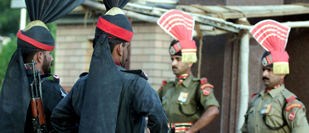 Pakistani (L) and Indian soldiers stand guard during the daily flaglowering ceremonies at the Wagah border between the nuclear rivalnations of Pakistan and India, some 20 km to the east of Lahore, theprovincial capital of Punjab June 23, 2002. Each day as the sun sets,the paramilitary guards on either side come nose-to nose, bristlingwith threat as noisy, partisan crowds cheer them on in a flag-loweringceremony at which they try to outdo each other in slamming shut theirrespective gates. REUTERS/Mohsin RazaMK/WS - RP3DRIFURPAA