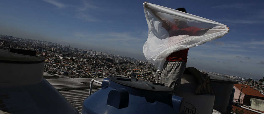 A man holds a mosquito net before placing it over a water container on the roof of his house, inside his house in Brasilandia slum in Sao Paulo February 11, 2015.