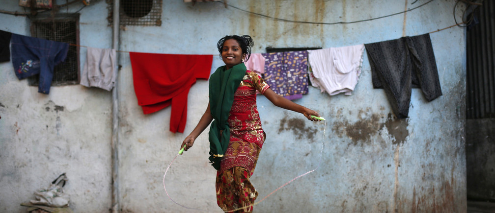 A girl jumps rope outside her house in Dharavi, one of Asia's largest slums, in Mumbai January 24, 2014.