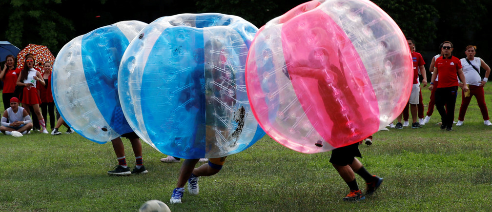Employees of a company and their families play a friendly game of bubble bump soccer at the University of the Philippines school campus in Quezon city, Metro Manila, Philippines June 14, 2016.   REUTERS/Erik De Castro - S1AETJZANBAB