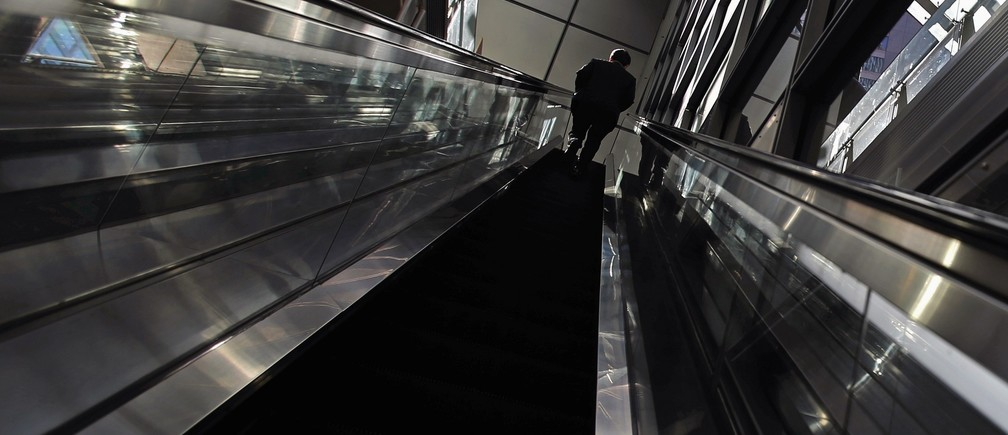 A man rides an escalator at Tokyo's business district December 8, 2014. Japan's economy shrank more than initially reported in the third quarter on declines in business investment, data showed on Monday, surprising markets and backing premier Shinzo Abe's recent decision to delay a second sales tax hike. REUTERS/Yuya Shino (JAPAN - Tags: BUSINESS) - RTR4H2EP