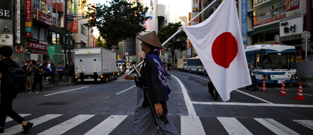 A Japanese soccer fan wearing samurai costume walks on the crossing after the World Cup Round of 16 soccer match Belgium vs Japan, at Shibuya district in Tokyo, Japan July 3, 2018. REUTERS/Issei Kato     TPX IMAGES OF THE DAY - RC1AD637C620
