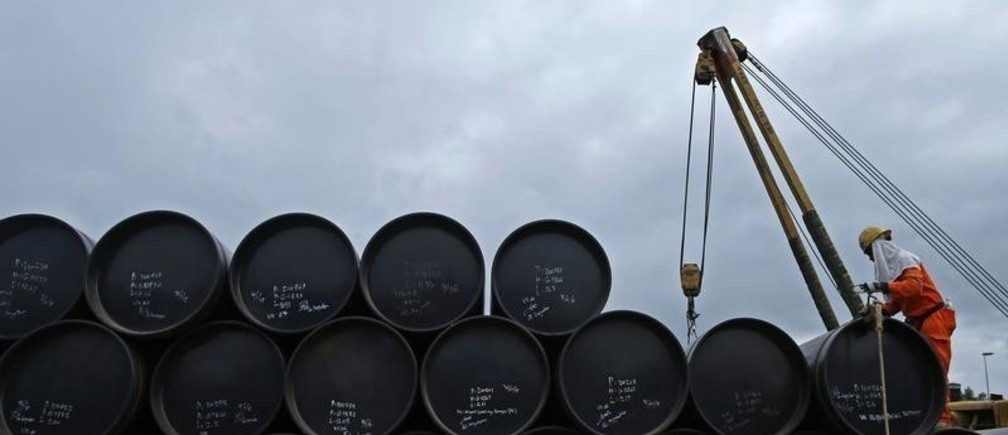 A worker prepares to transport oil pipelines to be laid for the Pengerang Gas Pipeline Project at an area 40km (24 miles) away from the Pengerang Integrated Petroleum Complex in Pengerang, Johor, February 4, 2015. A collapse in oil prices is making it harder to attract investment in the next phases of a plan to build one of Asia's biggest energy hubs on Malaysia's southernmost tip, a development estimated to be worth over $50 billion. The Pengerang Integrated Petroleum Complex (PIPC) aims to help Malaysia compete with Singapore to become the region's top oil and petrochemicals hub, but the local government body coordinating the project said the environment was now clearly tougher. On the once-sleepy Pengerang peninsular in the southern Johor state, villages have been relocated to make way for storage tanks, refineries and terminals under the almost $30 billion first phase. Picture taken February 4, 2015.  REUTERS/Edgar Su (MALAYSIA - Tags: BUSINESS COMMODITIES ENERGY CONSTRUCTION REAL ESTATE) - GM1EB2R0FES01