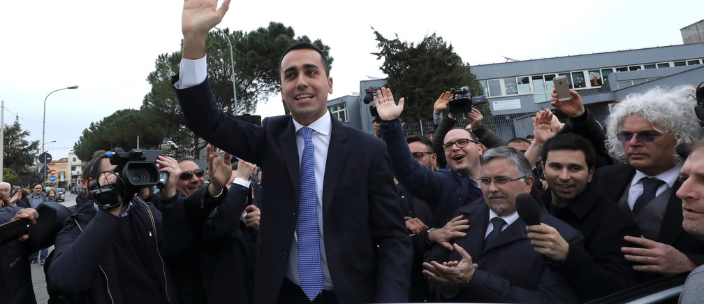 Five-Star Movement leader Luigi Di Maio waves after casting his vote.