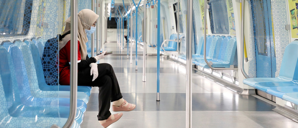 A woman wearing protective mask and gloves, uses her phone in a Mass Rapid Transit train, during the movement control order due to the outbreak of the coronavirus disease (COVID-19), in Kuala Lumpur, Malaysia March 22, 2020. REUTERS/Lim Huey Teng     TPX IMAGES OF THE DAY - RC2WOF9XOBQ3
