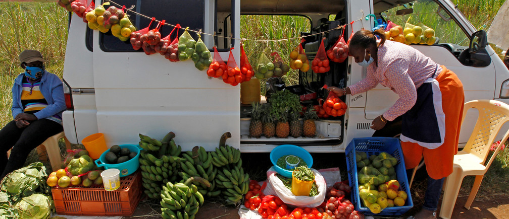 A motorist arranges fruits and vegetables for sale next to her vehicle, as an alternative mobile grocery stall, along the highway, following a lockdown due to the coronavirus disease (COVID-19) outbreak, on the outskirts of Nairobi, Kenya May 25, 2020.