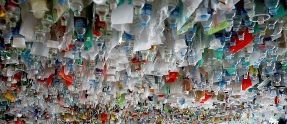 A girl attends a hanging art installation made from scraps of plastic bags, bottles, cans and containers at an exhibition entitled Reduce, at the French Cultural Center in Hanoi, Vietnam August 2, 2019. REUTERS/Kham - RC1BEFFCD7E0