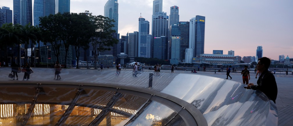 People pass the skyline of the central business district at the Marina Bay Promenade area in Singapore April 10, 2017.