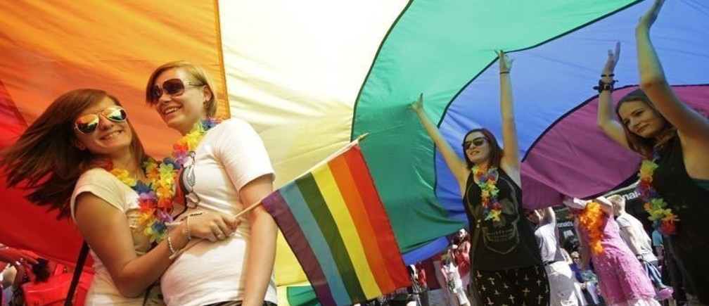 Participants stand underneath a rainbow-colored flag during the Prague Pride Parade where several thousand people marched through Prague's city centre in support of gay rights August 17, 2013.
