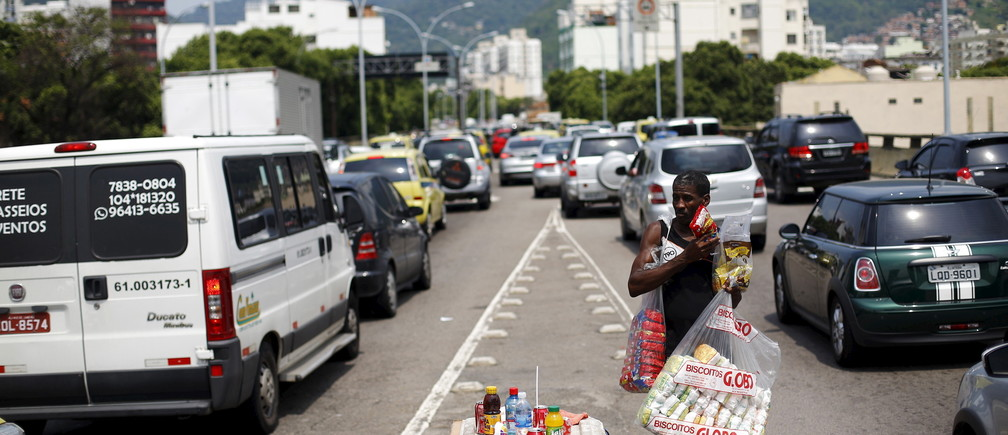 A street vendor holds goods for sale among cars during a traffic jam in Rio de Janeiro March 19, 2015.