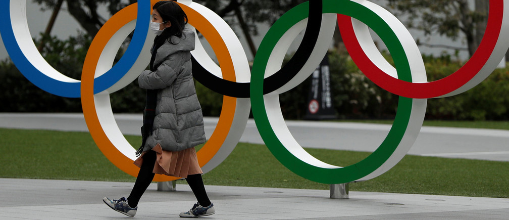 A woman wearing a protective face mask, following an outbreak of the coronavirus disease (COVID-19), walks past the Olympic rings in front of the Japan Olympics Museum, in Tokyo, Japan March 30, 2020. REUTERS/Issei Kato - RC24UF9610O6