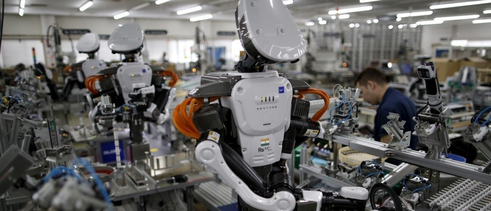 Humanoid robots work side by side with employees in the assembly line at a factory of Glory Ltd., a manufacturer of automatic change dispensers, in Kazo, north of Tokyo, Japan
