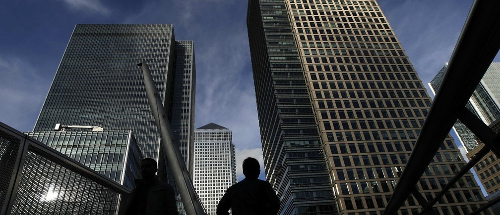 Silhouetted workers walk in front of office towers in the Canary Wharf financial district in London.