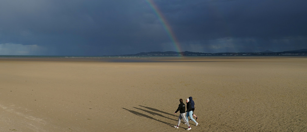 A rainbow and heavy rain are seen in the distance as people walk along an empty beach in sunshine, following the outbreak of the coronavirus disease (COVID-19), in Dublin, Ireland, June 5, 2020. REUTERS/Clodagh Kilcoyne - RC293H98WKRB