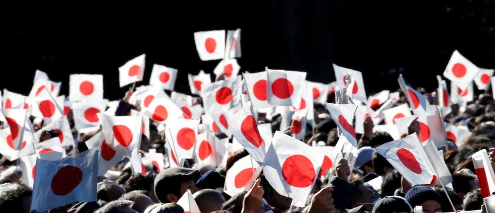 Well-wishers wave Japanese national flags as Japan's Emperor Akihito makes an appearance for the New Year celebrations at the Imperial Palace in Tokyo.