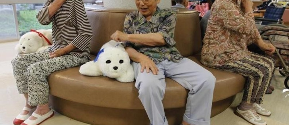 Ayako Shizo (C), aged 85, taps a therapeutic robot named Paro as she sits with other residents at the Suisyoen retirement home about 30 km (19 miles) south of the tsunami-crippled nuclear plant in Iwaki, Fukushima prefecture, July 28, 2011. For some elderly survivors of Japan's March earthquake and tsunami, comfort comes in the form of a small white robotic seal named Paro. The residents of the nursing home came back from a nearly two-month-long evacuation since the nuclear crisis in Fukushima.  Picture taken July 28, 2011. To match Reuters Life! ROBOT-SEAL/   REUTERS/Kim Kyung-Hoon (JAPAN - Tags: SOCIETY SCI TECH IMAGES OF THE DAY)
