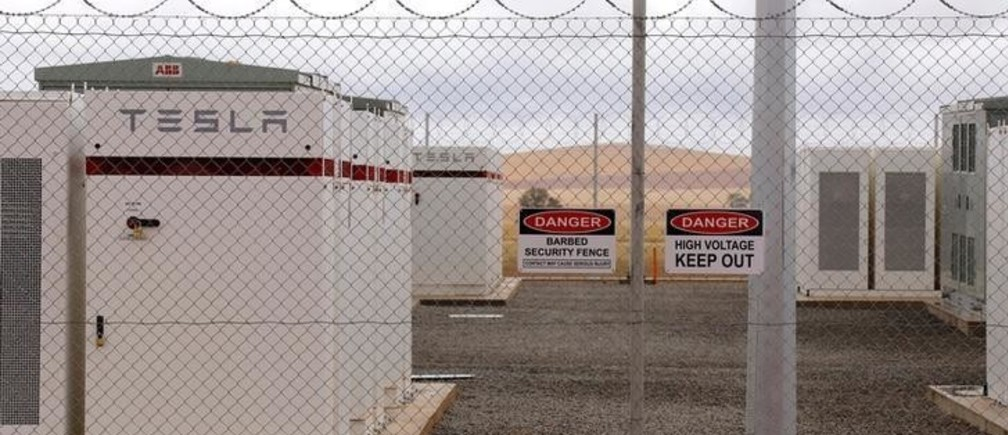 Warning signs adorn the fence surrounding the compound housing the Hornsdale Power Reserve, featuring the world's largest lithium ion battery made by Tesla, during the official launch near the South Australian town of Jamestown, in Australia, December 1, 2017.      REUTERS/David Gray