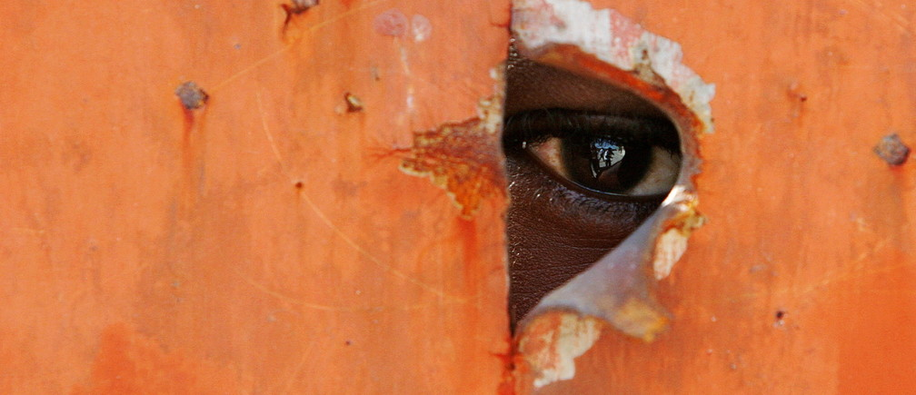 A Haitian looks through a hole at the new registration center as residents wait to register their names for the next presidential elections in the volatile neighborhood of Citi-Soleil, Haiti, October 6, 2005. - PBEAHUNWPEN