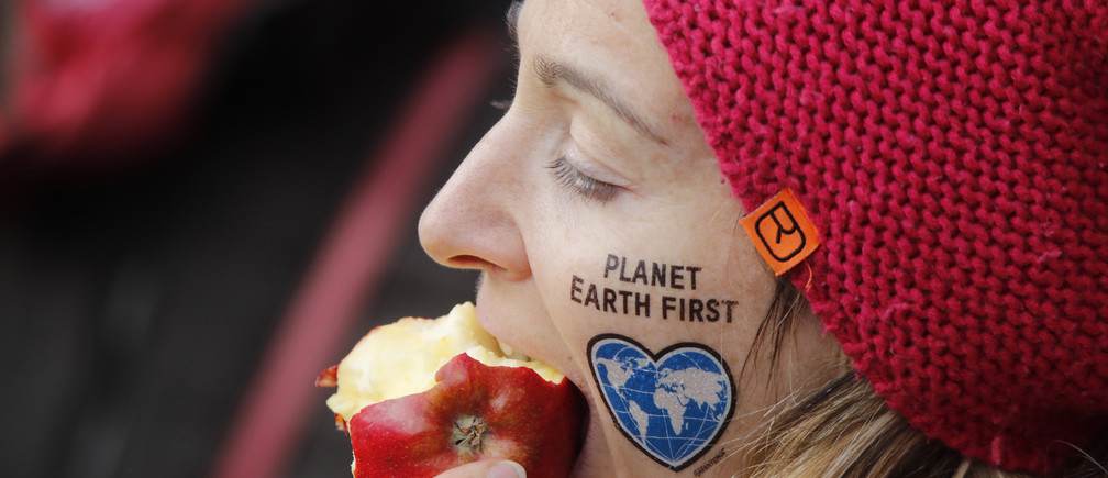 "A protester eats an apple during a demonstration under the banner ""Protect the climate - stop coal"" two days before the start of the COP 23 UN Climate Change Conference hosted by Fiji but held in Bonn, Germany November 4, 2017. - UP1EDB40ZF00Y"