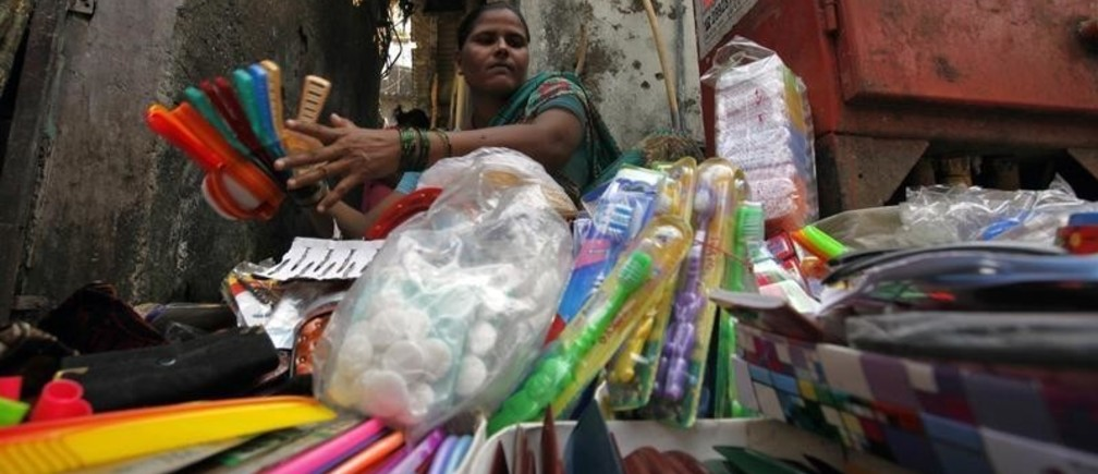 Tairabi Pathan, 40, who took a loan of rupees 10,000 ($220) from a micro finance company to start her own business, arranges her goods for sale at the side of a road in a slum area in Mumbai October 26, 2010. India's microfinance industry, which surged to prominence when George Soros-backed SKS Microfinance raised $358 million in an IPO, faces a regulatory clampdown that could erode profits and hurt growth. Reports of dozens of suicides by poor borrowers in the southern state of Andhra Pradesh, the hub of India's microfinance sector, prompted the state to enact an rules against aggressive recovery practices by lenders who make loans that average about $150 to poor customers at interest rates that can top 30 percent. Picture taken October 26, 2010.       To match analysis INDIA-MICROFINANCE/      REUTERS/Danish Siddiqui (INDIA - Tags: SOCIETY BUSINESS) - GM1E6AS11VZ01