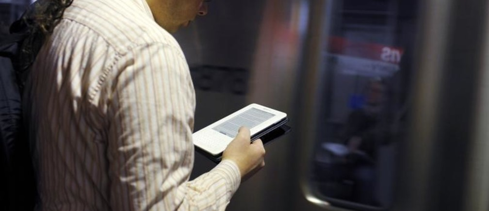 A commuter reads on his Kindle e-reader as a subway train arrives in Cambridge, Massachusetts, March 18, 2011. Publishers are adapting to rising sales of e-books, and the popularity of smart phones and tablets such as the iPad. The retail landscape has changed with Amazon becoming the dominant seller of books while countless book stores go the way of video rental stores. America's No. 2 book store chain, Borders, is bankrupt. Some authors have dropped their publishers entirely, self-publishing online and using social media to connect with readers. Picture taken March 18, 2011. To match Special Report PUBLISHING/EBOOKS/   REUTERS/Brian Snyder (UNITED STATES - Tags: MEDIA BUSINESS SCI TECH) - GM1E7411RP501