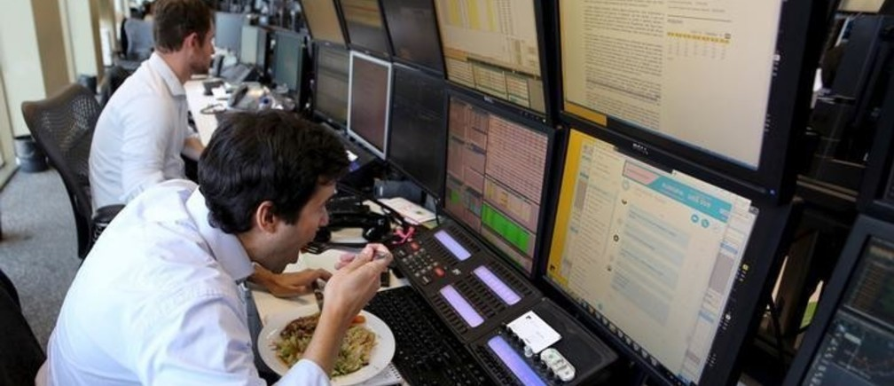 A trader eats lunch at his desk at a brokerage in Sao Paulo, Brazil, September 10, 2015. Brazil's financial markets fell on Thursday after Standard & Poor's cut the country's sovereign rating to junk late Wednesday, though assets began to pare losses in late morning trading as the downgrade had been largely priced in. REUTERS/Paulo Whitaker