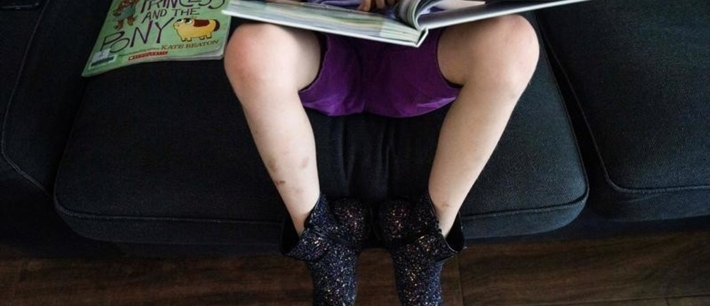 """Keegan, 8, who identifies as gender creative, reads at home near Austin, Texas, U.S., April 25, 2019. Keegan's favorite book is """"Prince + The Dressmaker."""" His parents have also included LGBTQ children's literature to his reading list. The objective, they say is to teach him LGBTQ-related history so that he can better understand what others went through and in turn appreciate his right to do things like wear dresses or do drag. They frequently check out the book """"Pride: Celebrating Diversity and Community"""" by Robin Stevenson, from the local library, which includes the history of Stonewall. REUTERS/Amanda Voisard    SEARCH """"GENDER CREATIVE"""" FOR THIS STORY. SEARCH """"WIDER IMAGE"""" FOR ALL STORIES. - RC19B9A2B450"""