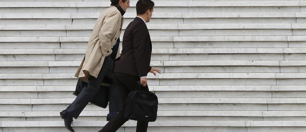 Businessmen carry briefcases as they climb the stairs under the Arche de la Defense in the financial and business district west of Paris October 21, 2014.   REUTERS/John Schults  (FRANCE - Tags: BUSINESS) - RTR4B05B
