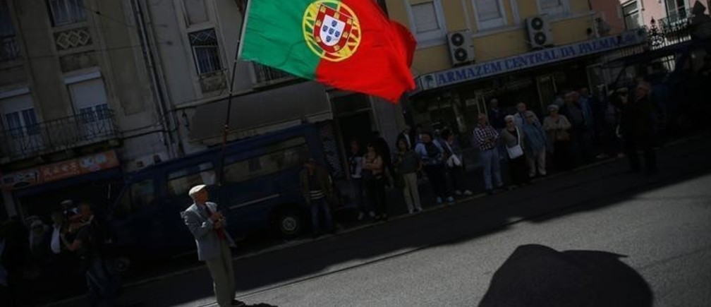 A demonstrator holds a Portuguese flag as he waits for the start of a May Day demonstration in Lisbon, Portugal May 1, 2017. REUTERS/Rafael Marchante