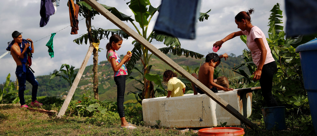 """Lisibeht Martinez (R), 30, who was sterilized one year ago, plays with her children in a bathtub in the backyard of their house in Los Teques, Venezuela July 19, 2016. REUTERS/Carlos Garcia Rawlins SEARCH """"STERILIZATION CHILD"""" FOR THIS STORY. SEARCH """"THE WIDER IMAGE"""" FOR ALL STORIES.  - RTSKV3N"""