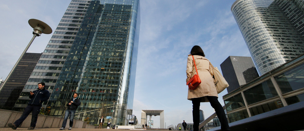 A businesswoman walks at La Defense business and financial district in Courbevoie near Paris.