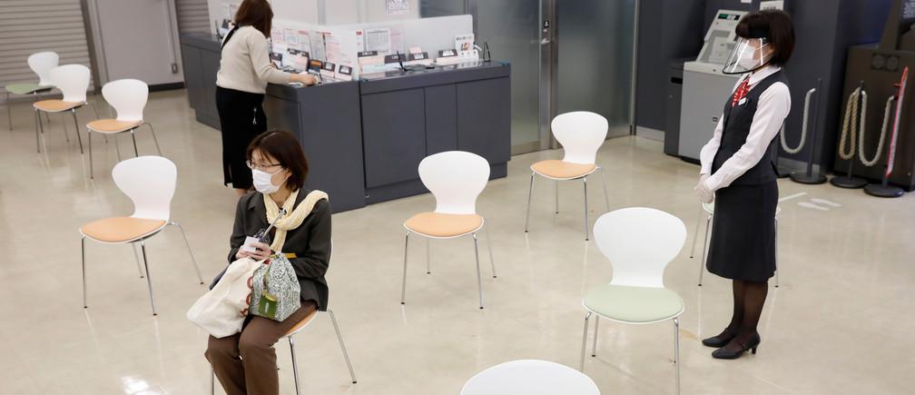 Una cliente se sienta en una de las sillas que se establecieron para mantener el distanciamiento social con el fin de prevenir las infecciones tras el brote de la enfermedad coronavirus (COVID-19), en la sucursal de Higashinakano del Banco MUFG en Tokio, Japón, el 24 de abril de 2020.