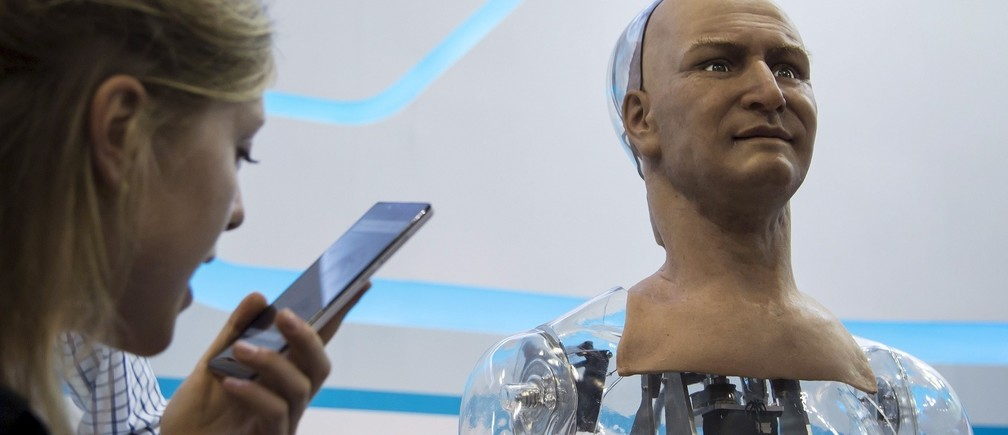 A staff talks to a humanoid robot named Han developed by Hanson Robotics via a mobile phone during the Global Sources spring electronics show in Hong Kong April 18, 2015. According to Hanson Robotics the robot's skin is made out of a material called Frubber, an elastic polymer that mimics the human skin, and installed with about 40 motors on its face which help create various expressions. Han can answer simple questions and staff said it can be used in the field of customer service. The show ends on April 21. REUTERS/Tyrone Siu - RTR4XU26