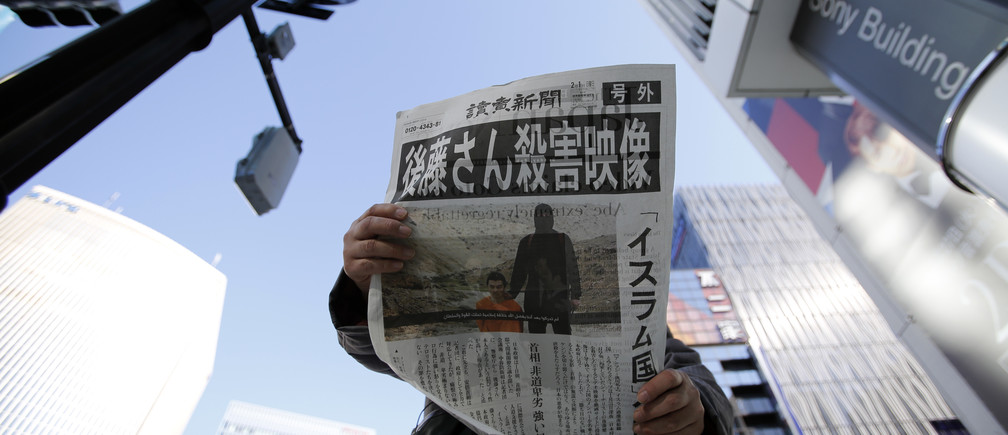 A man reads an extra edition of a newspapers, which reported that Islamic State militants said they had beheaded Japanese journalist Kenji Goto, in Tokyo's Ginza district February 1, 2015. Islamic State militants said on Saturday they had beheaded a second Japanese hostage, journalist Kenji Goto, after the failure of international efforts to secure his release through a prisoner swap.  REUTERS/Toru Hanai (JAPAN - Tags: POLITICS CRIME LAW CIVIL UNREST TPX IMAGES OF THE DAY) - GM1EB210RGZ01