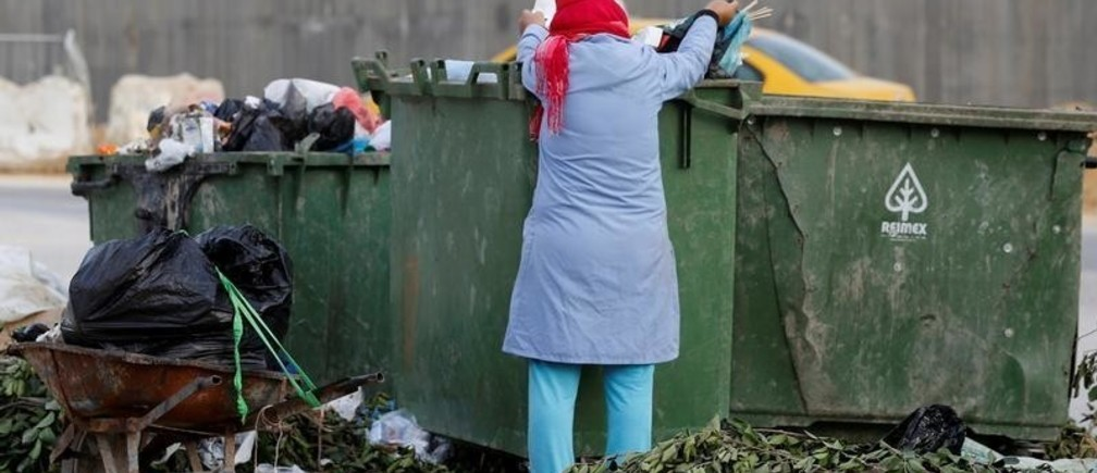 A women collects plastic bottles from a garbage bin in Tunis, Tunisia November 23, 2019. Picture taken November 23, 2019. REUTERS/Zoubeir Souissi - RC2SND9QPFCH