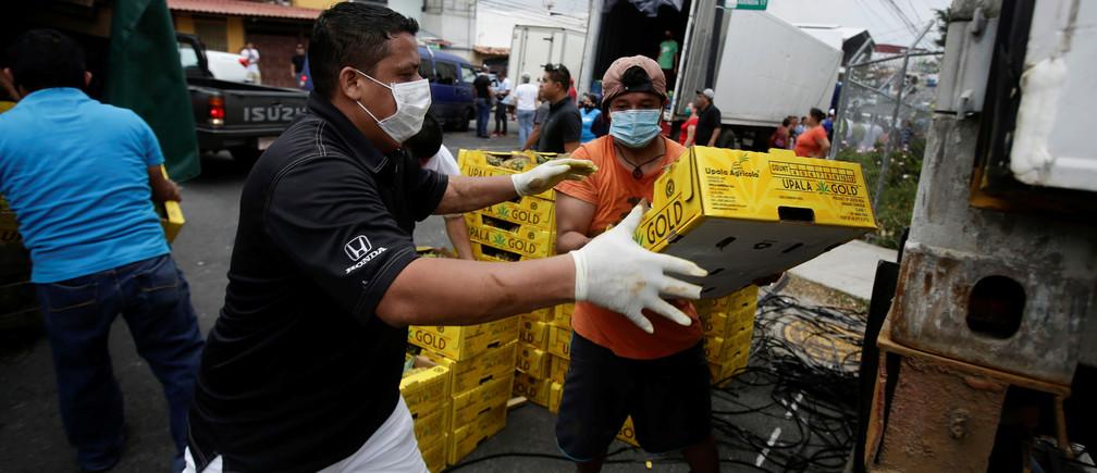 Trabajadores descargan piñas en un punto de distribución de frutas y verduras donadas por productores nacionales que no pueden exportar debido a la enfermedad coronavirus (COVID-19), en San José (Costa Rica) el 13 de abril de 2020.