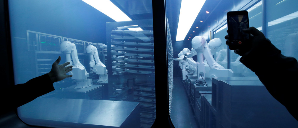 A customer takes a picture as robotic arms collect pre-packaged dishes from a cold storage, done according to the diners' orders, at Haidilao's new artificial intelligence hotpot restaurant in Beijing, China, November 14, 2018. Picture taken November 14, 2018. REUTERS/Jason Lee - RC13639C1D90