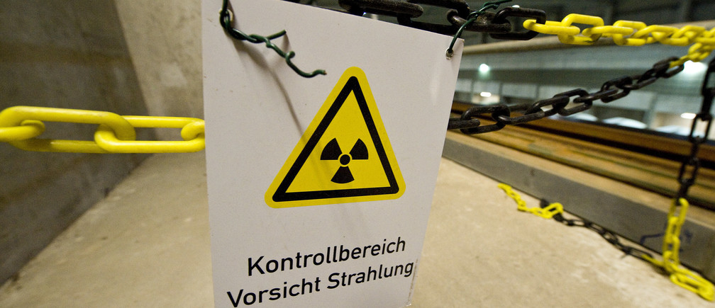 A warning sign for radioactive materials is seen in the warehouse for 'Castor' containers at 'Zwischenlager Gorleben' temporary nuclear waste storage facility in the northern German village of Gorleben near Dannenberg August 5, 2010. The storage facility was constructed to hold about 420 Castor containers of highly radioactive reprocessed German nuclear waste. Sign reads : 'Controlled Area. Warning Radiation'    REUTERS/Morris Mac Matzen (GERMANY - Tags: ENERGY) - BM2E68517TF01