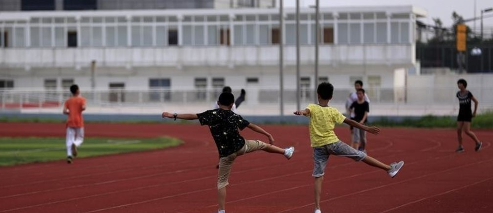 Youths attend a daily track-and-field class, part of a training course at the Jinshan Youth Spare-time Sports School, in Shanghai, August 25, 2015. About 30 youths, between 10 and 14 years old, are enrolled in the course where the top participants will be selected to be groomed to become professional athletes. REUTERS/Aly Song - GF10000181949