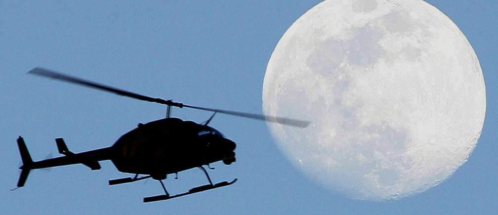 A news helicopter flies past the full moon shining over Miami in a photo taken January 23, 2005. NO RIGHTS CLEARANCES OR PERMISSIONS ARE REQUIRED FOR THIS IMAGE. REUTERS/Marc Serota  MS/JRB - RP5DRIGFBGAA