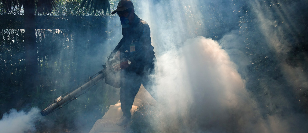 A worker sprays insecticide for mosquitos at a village in Bangkok, Thailand, December 12, 2017. Picture taken December 12, 2017.