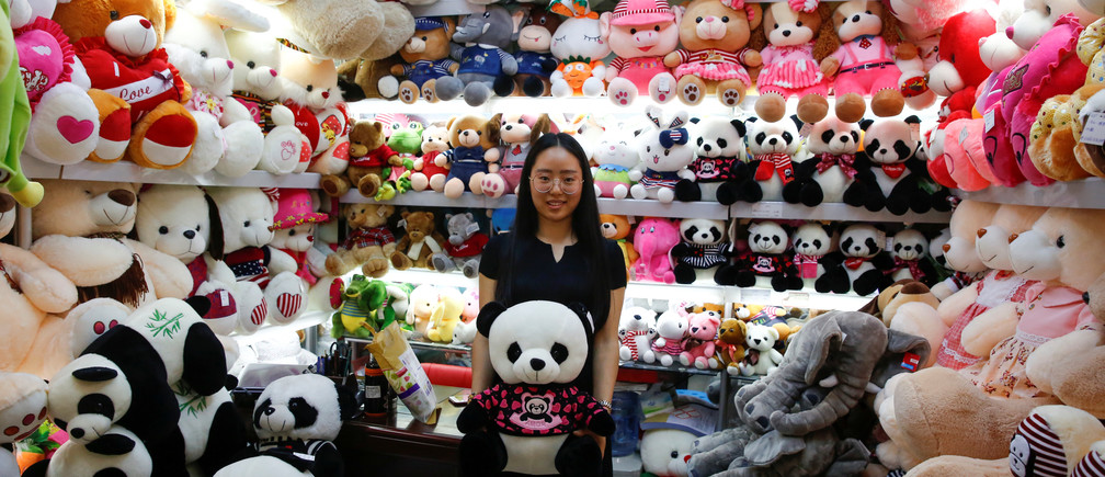 A staff member holds a Panda soft toy as she poses for a picture in a stall at the Yiwu Wholesale Market in Yiwu, Zhejiang province, China, April 28, 2017. Picture taken April 28, 2017. REUTERS/Thomas Peter - RTS14F4T