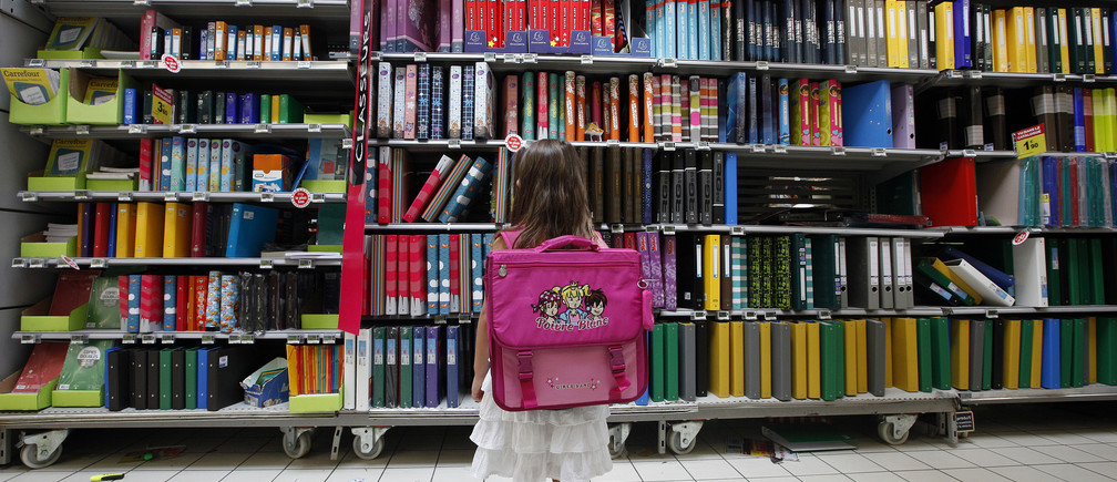 A young girl looks at school stationery in a supermarket in Nice August 23, 2012. The new school year will start on September 4 in France.
