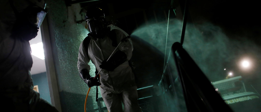Workers wearing protective suits spray disinfectant solution at a medical facility during the national quarantine in response to the spread of coronavirus disease (COVID-19) in Caracas, Venezuela March 22, 2020. REUTERS/Manaure Quintero