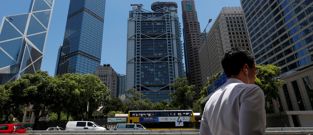 A man walks in front of the (L-R) Bank of China Tower, Cheung Kong Center, HSBC bank and Standard Chartered bank at the financial central district in Hong Kong, China June 24, 2016.    REUTERS/Bobby Yip - RTX2HX4H