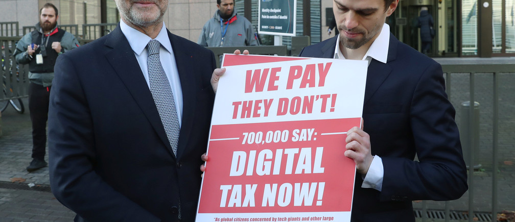 European Commissioner for Economic and Financial Affairs Pierre Moscovici receives the petition regarding the digital tax from the representative of the global activism group Avaaz, outside the EU headquarters in Brussels, Belgium, December 4, 2018. REUTERS/Yves Herman - RC1B6E422E60