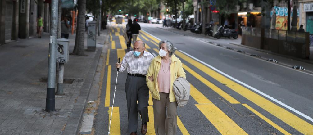 Una pareja de ancianos con máscaras faciales camina por una acera marcada para que los peatones guarden distancia social, durante las horas en que se permite a los ancianos estar al aire libre, mientras continúa la propagación de la enfermedad coronavirus (COVID-19), en Barcelona, España, el 11 de mayo de 2020.