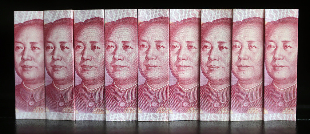 Chinese 100 yuan banknotes are seen in this picture illustration taken in Beijing July 11, 2013. China's central bank has standardised rules on cross-border yuan transactions for domestic banks and companies, the latest step to boost the yuan's global influence. REUTERS/Jason Lee (CHINA - Tags: BUSINESS TPX IMAGES OF THE DAY) - GM1E97B0Z1M01