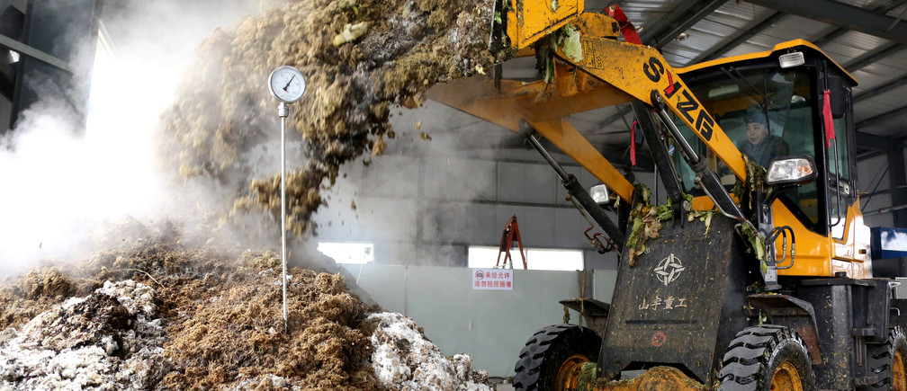 A worker operates a front loader at a waste treatment facility that turns vegetable waste into fertilizers, in Zaozhuang, Shandong province, China December 25, 2018. Picture taken December 25, 2018. REUTERS/Stringer  ATTENTION EDITORS - THIS IMAGE WAS PROVIDED BY A THIRD PARTY. CHINA OUT. - RC1D688F5E40